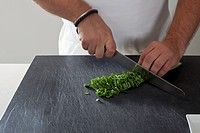 Detail of a man chopping fresh herbs
