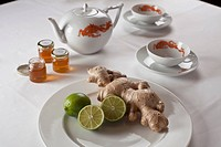 Raw ginger and limes on a plate next to teapot and cups