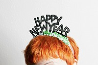 A woman wearing a party tiara with Happy New Year on it, top of head (thumbnail)