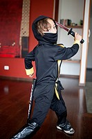 A boy dressed in a ninja costume swinging a samurai sword (thumbnail)