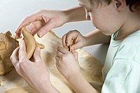 Mother gives son a helping hand with play clay