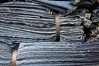 Bunch of binded blue jeans layer together.