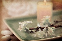 Delicate spring cherry blossoms, towel and candle in a zen spa atmosphere. Old photo style