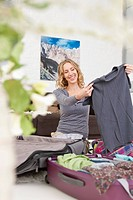 Germany, Leipzig, Mid adult woman packing suitcase, smiling (thumbnail)