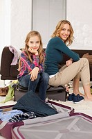 Germany, Leipzig, Mother and daughter sitting on suitcase, smiling