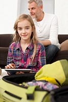 Germany, Leipzig, Father and daughter with digital tablet in apartment