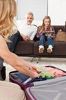 Germany, Leipzig, Woman packing suitcase and father and daughter in background