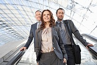 Germany, Leipzig, Business people on escalator, smiling