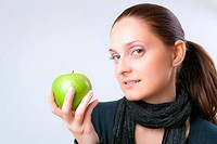 Beautiful elegant young lady with a charming smile and soft relaxing expression shows fresh ripe green apple placed in her hand