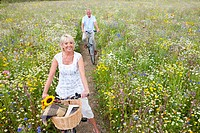 Smiling senior couple riding bicycles on path through field of wildflowers