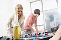 Germany, Cologne, Young women playing table soccer, smiling (thumbnail)