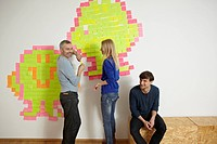 Germany, Cologne, Men and woman with paper note on wall