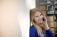 Germany, Cologne, Young woman on cell phone, smiling