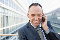 Germany, Leipzig, Businessman on cell phone, smiling, portrait