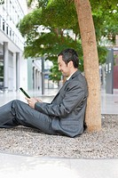 Germany, Leipzig, Businessman sitting at tree and using digital tablet (thumbnail)