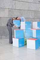 Germany, Leipzig, Business people resting on cubes