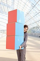 Germany, Leipzig, Businesswoman with cubes, smiling, portrait (thumbnail)