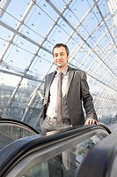 Germany, Leipzig, Businessman on escalator, portrait (thumbnail)