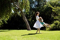 Mother swinging daughter in park