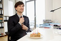 Germany, Cologne, Mid adult man with birthday cake, smiling