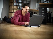 Germany, Cologne, Mid adult man using laptop