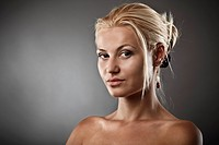 Closeup portrait of a beautiful blonde on gray background