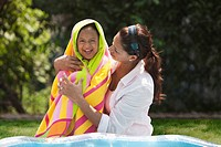 Hispanic woman wrapping daughter in towel