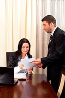 Business man giving a contract for signing to a business woman sitting on chair at table