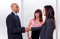 Business team of three, man and woman shaking hands and smiling.