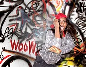 Black woman dancing near graffitied wall