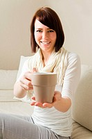 Young woman holding a hot cup of tea
