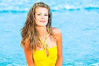 Beautiful woman in yellow dress on the beach