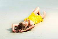 Beautiful woman in yellow dress on the beach