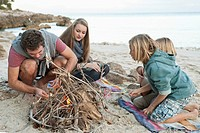 Spain, Mallorca, Friends preparing camp fire on beach