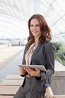 Germany, Leipzig, Businesswoman with digital tablet, smiling