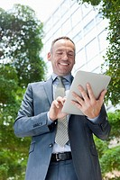Germany, Leipzig, Businessman using digital tablet, smiling