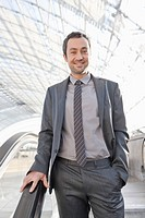Germany, Leipzig, Businessman on escalator, smiling, portrait
