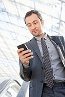 Germany, Leipzig, Businessman using cell phone on escalator