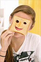 beautiful teenage girl, hiding behind a toast with cut mouth and eyes