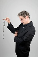 Businessman wearing a black suit looking at open handcuffs