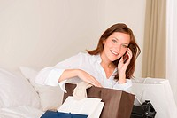 Woman on phone _ back home from shopping sitting on bed