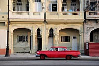 Red classic car of the 1950's on the Malecon esplanade, Avenida de Antonio Maceo, a boulevard in the city centre of Havana, Centro Habana, Cuba, Great...