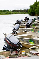 Outboard motors on skiffs lining the bank of the Mulchatna River near a sportfishing camp, Southwest Alaska, Summer