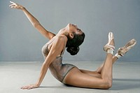 Ballet dancer posing on floor