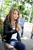 Girl holding a glass bottle of mineral water and resting