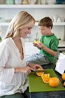 Mother slicing oranges for son (thumbnail)