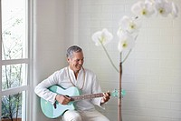Smiling older man playing guitar
