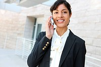 A pretty african american business woman at her office building on phone