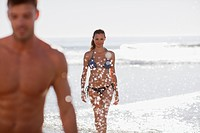 Woman in bikini walking in waves