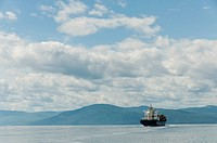 scenic view of St Lawrence river near Quebec city with container ship coming from Panama, under a beautiful blue sky